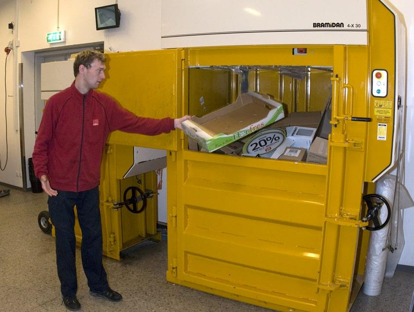 Man from SuperBrugsen fills Bramidan baler with cardboard