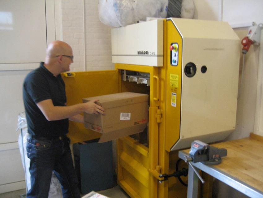 Man fills cardboard boxes into yellow Bramidan baler
