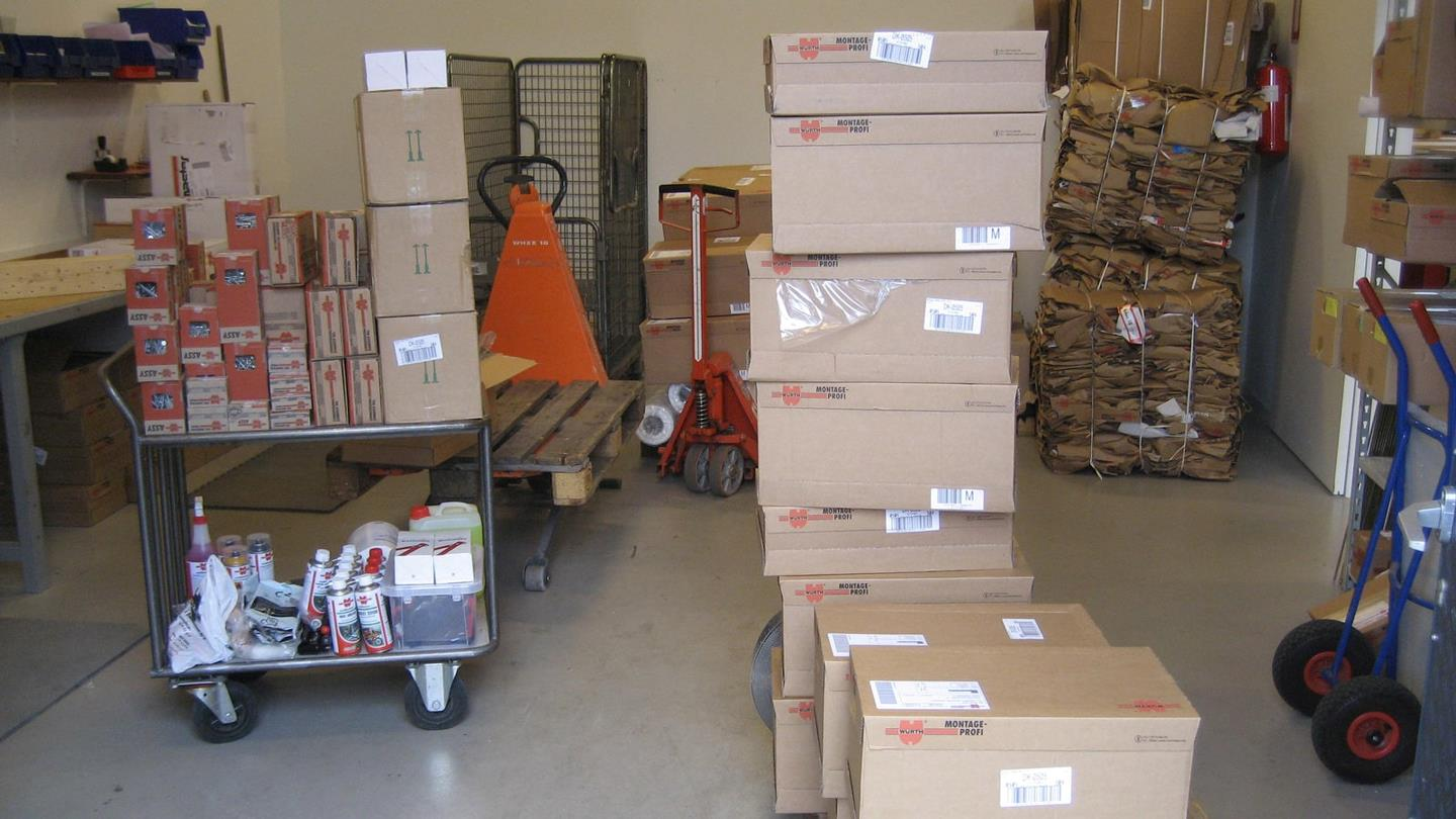 Boxes with goods and stacked cardboard bales in Würth storage room
