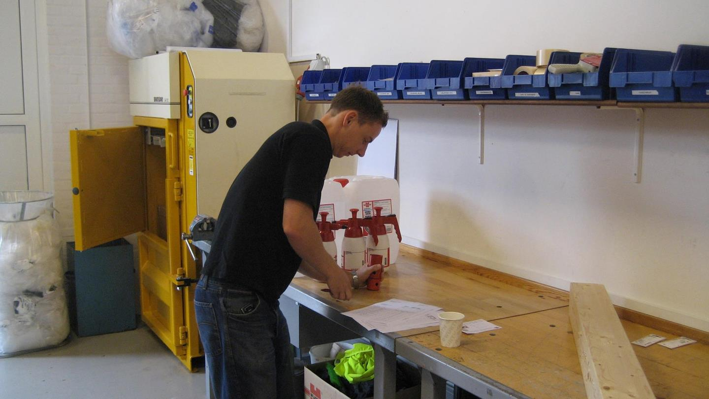 Würth employee works at packing table next to Bramidan baler